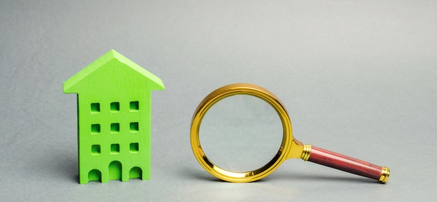 Miniature wooden house and magnifying glass.