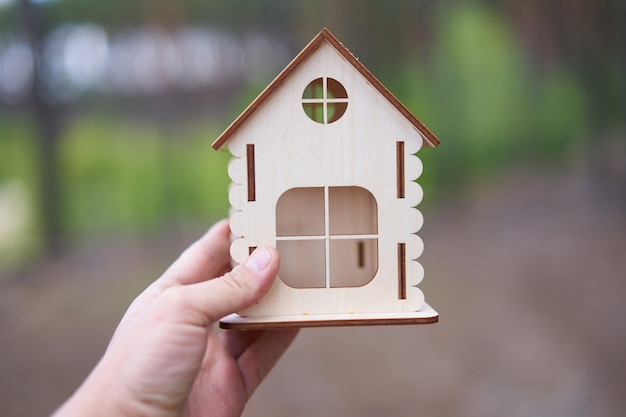 Miniature wooden house in a male hand