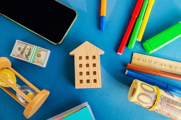 Миниатюрный деревянный домик на деньги и песочные часы. концепция недвижимости