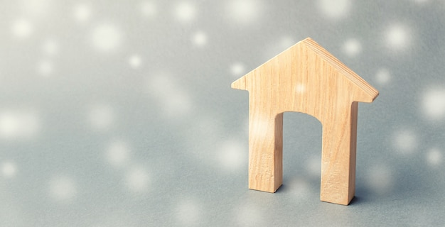 Miniature wooden house and snowflakes. demand for real estate in the winter.