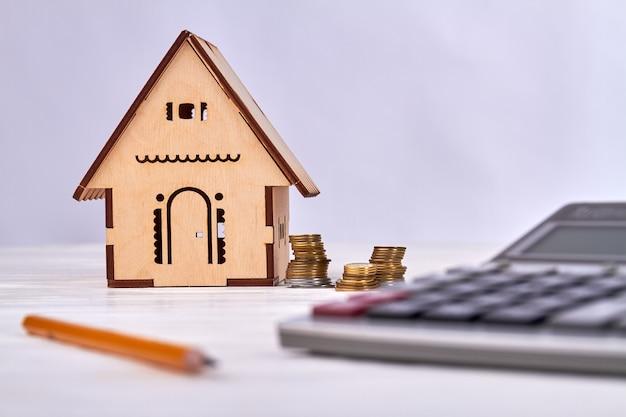 電卓、コイン、白いテーブルに鉛筆でミニチュア木造住宅。