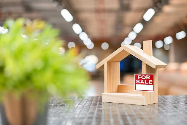 Miniature wooden house with for sale sticker