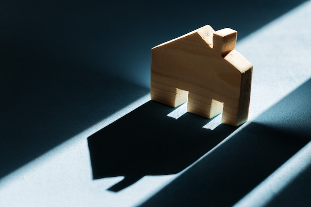 Miniature wooden house with shadows on blue background close up