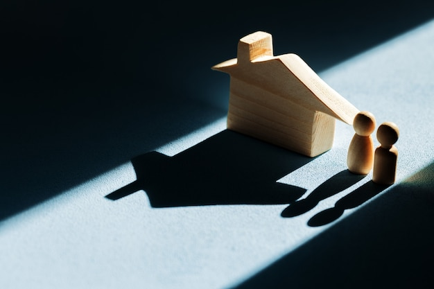 Miniature wooden house with shadows on blue background