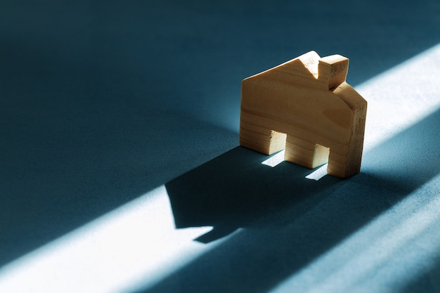 Miniature wooden house with shadows on blue