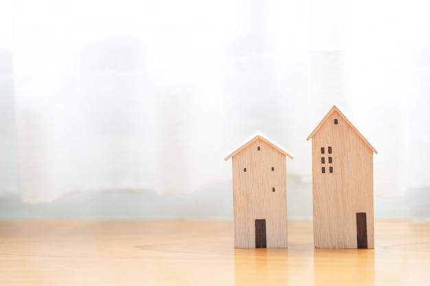木製テーブルの上のミニチュア木造住宅モデル