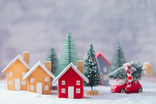 Miniature wooden houses and small red car with fir tree on the snow over blurred christmas decoration