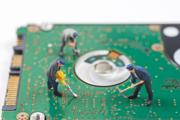 Miniature worker are digging a hole on hard disk electronic board