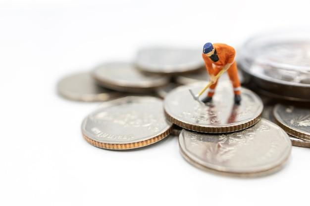 コインスタックを掘るミニチュア労働者。お金と投資の概念。
