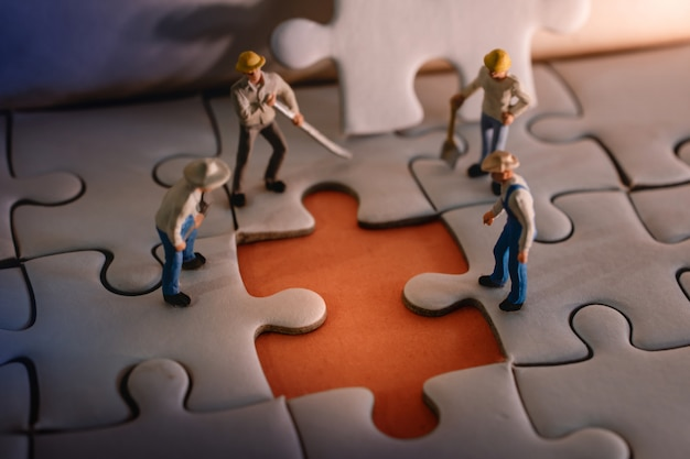 Miniature worker men found a wrong on jigsaw puzzle