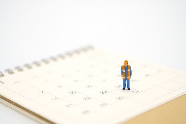 Miniature worker standing on white calendar