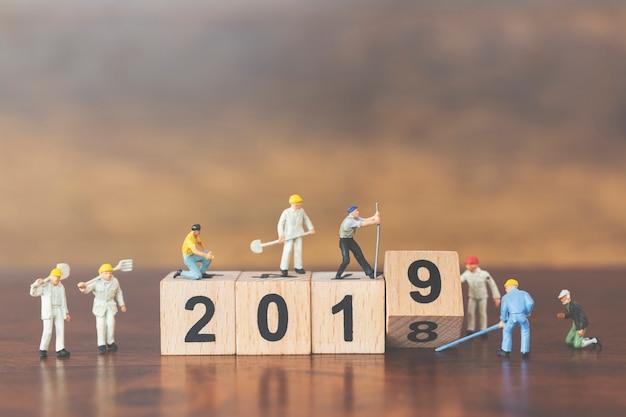 Miniature worker team building wooden block number 2019