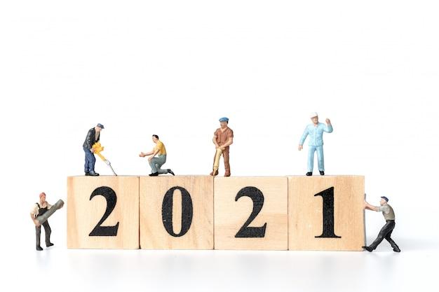 Miniature worker team create wooden block number 2021