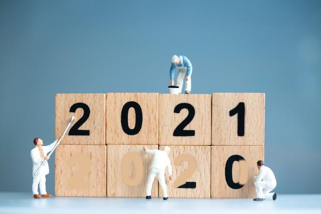 ミニチュア労働者チームは番号2021をペイントし、番号2020を削除し、新年あけましておめでとうございますのコンセプト
