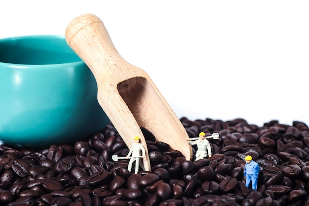 Miniature worker working on fresh coffee beans on white background .