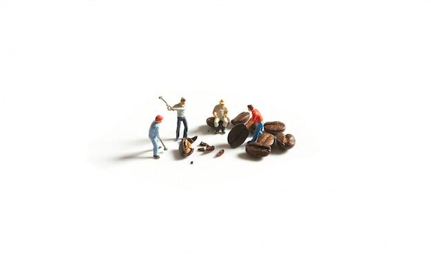 Миниатюрные рабочие измельчают кофейные зерна.