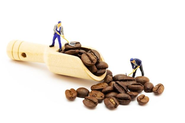 나무 국자 숟가락에 커피 콩을로드하는 소형 노동자. 커피 타임 컨셉입니다.