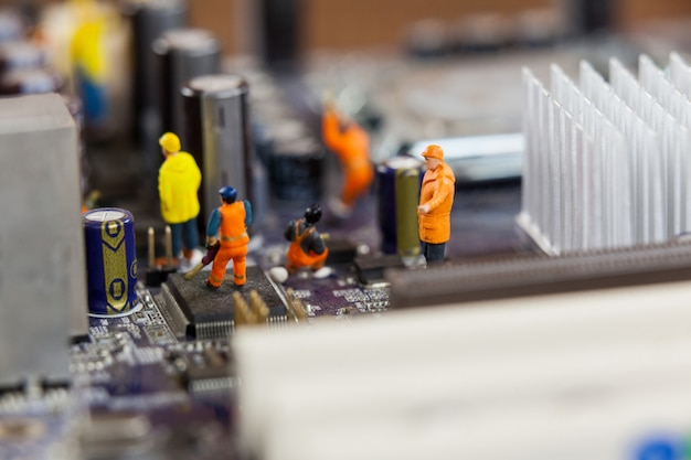 Miniature workers working on chip of motherboard