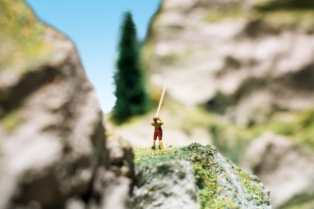 Miniature world of a young man playing long trumpet in the mountains