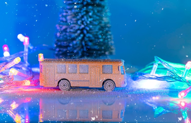 Miniature yellow bus and fir tree during snowfall, imitation of night time with garland
