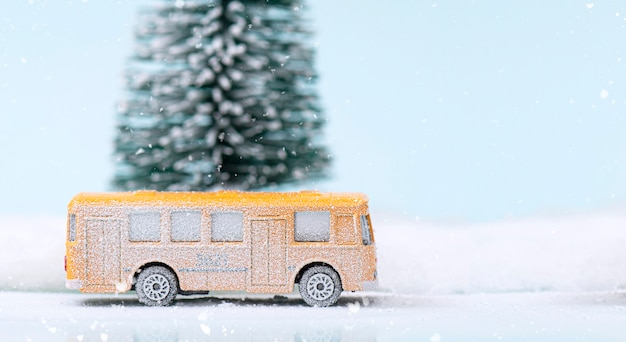 Miniature yellow bus and fir tree during snowfall
