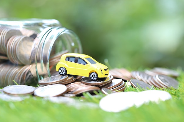 Miniature yellow car model on stack of coins money in glass bottle on nature green background