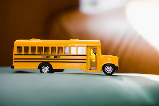 Miniature yellow school bus with sunlight