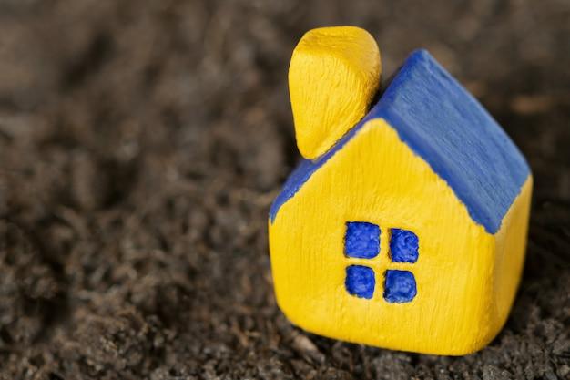 어두운 토양에 파란 지붕 가진 소형 노란색 장난감 집. 선택적 초점.