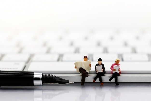 Miniatures people reading with keyboard, education or business concept.