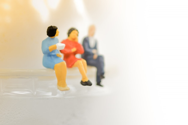 Miniatures of people sitting on a cup of coffee with drink coffee