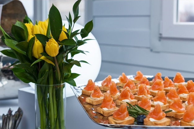 Minicanapes with smoked salmon and razmorinom on a silver platter for a party