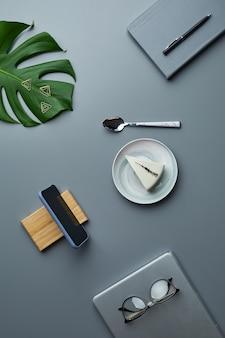 Минимальная плоская планировка чизкейка и бизнес-аксессуаров на сером фоне рабочего места с тропическими листьями