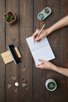 テクスチャード加工の木製の職場の背景の上にプランナーで書いている女性の手のフラットレイのビューの最小上に、