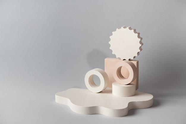 製品プレゼンテーションのための最小限の抽象的な化粧品の背景。灰色の背景に化粧品ボトルの表彰台。パステルカラーは、幾何学的な形で構成をスタイリングしました。最小限のコンセプト。製品のモックアップ