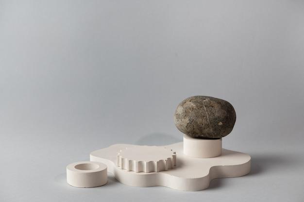 製品のプレゼンテーションのための石で最小限の抽象的な化粧品の背景。灰色の背景に化粧品ボトルの表彰台。幾何学的な形の構成。最小限のコンセプト。製品のモックアップ