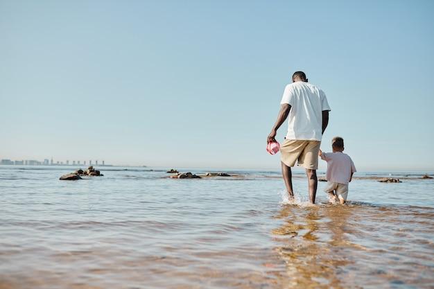 ビーチのコピースペースで水の上を歩く若い父と息子の最小限の背面図の肖像画