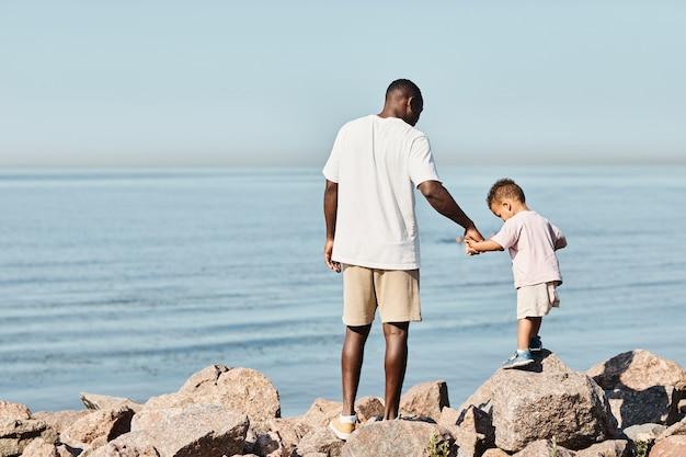 最小限の背面図の肖像画ビーチで遊んでいる間かわいい息子を抱いている若いアフリカ系アメリカ人の父は...