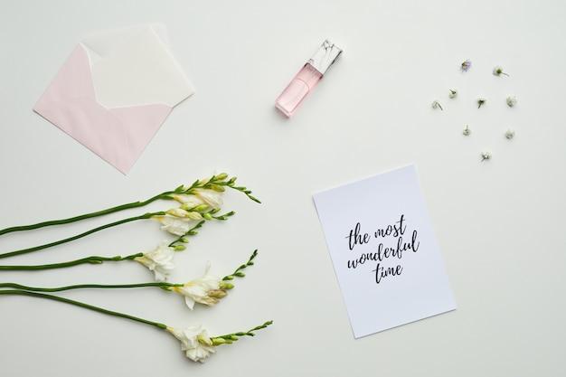 花のディテールと最も素晴らしい時間をレタリングするテーブル上の封筒と香水の最小限の背景構成、