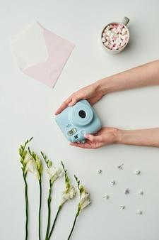 Минимальная фоновая композиция из женских рук, держащих мгновенную камеру над фоном стола с цветочными акцентами и чашкой какао,