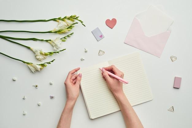 花の装飾が施されたテーブルの背景に対してプランナーで書く女性の手の最小限の背景構成、