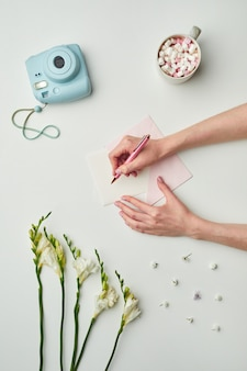 Минимальная фоновая композиция женских рук, пишущих письмо, пока фон стола с цветочными акцентами и чашкой какао,