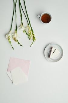 Минимальная фоновая композиция письма с конвертом и украшенная цветочным акцентом,