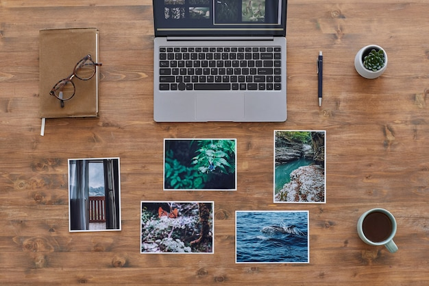 Minimal background composition of printed photographs and laptop on textured wooden desk, photographers office, copy space