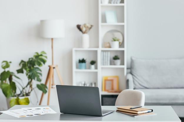 Минимальное фоновое изображение домашнего офиса на рабочем месте с ноутбуком в белом просторном интерьере, копией пространства