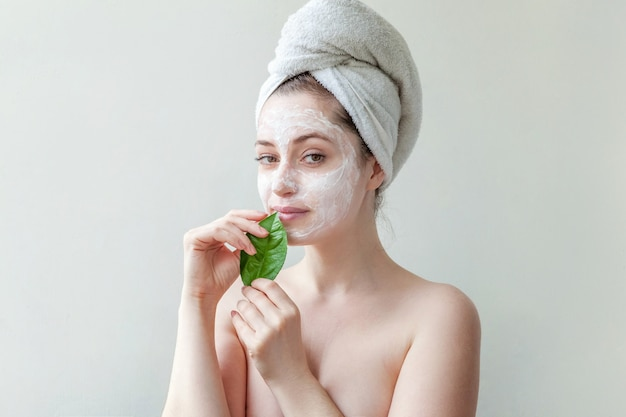 얼굴에 흰색 영양 마스크 또는 크림을 적용하는 머리에 수건에 최소한의 아름다움 초상화 여자 소녀, 손에 녹색 잎 격리 된 흰 벽. 스킨 케어 클렌징 에코 유기농 화장품 스파 개념.