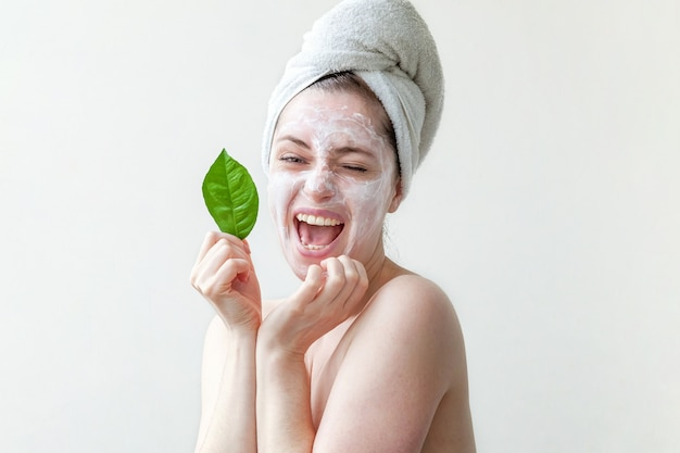 Minimal beauty portrait woman girl in towel on head applying white nourishing mask or creme on face, green leaf in hand isolated white background.