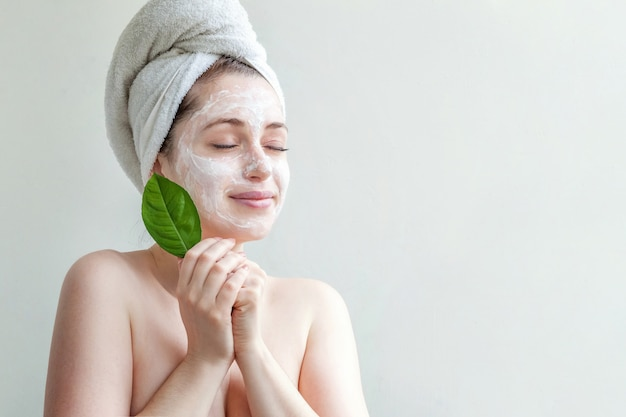 Minimal beauty portrait woman girl in towel on head applying white nourishing mask or creme on face, green leaf in hand isolated white wall. skincare cleansing eco organic cosmetic spa concept.