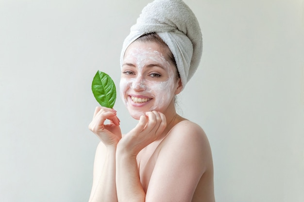 Minimal beauty woman girl in towel on head portrait applying white nourishing mask or creme on face, green leaf in hand isolated white background.