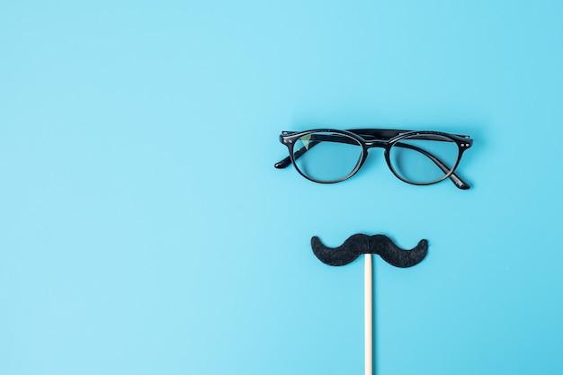 青の背景に最小限の黒い口ひげと眼鏡。幸せな父の日と国際男性デーの概念