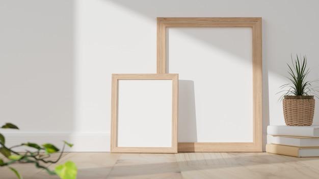 Минимальные пустые деревянные рамы для картин на деревянном полу с книгами, плетеным горшком с растением и белой предпосылкой стены. 3d рендеринг, 3d иллюстрации